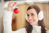 Pretty brunette with ear muffs holding bauble