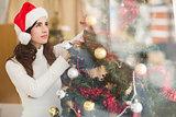 Festive brunette decorating a christmas tree