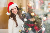 Smiling brunette decorating a christmas tree
