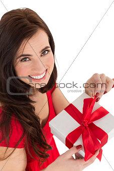 Smiling brunette opening gift