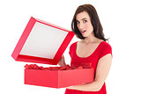 Surprised brunette in red dress opening gift