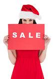Brunette in red dress holding sale sign