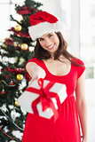 Festive brunette in red dress holding gift at christmas