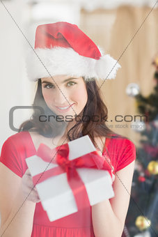 Beauty brunette showing gift at christmas