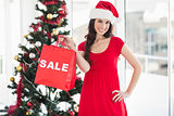 Stylish brunette in red dress showing sale bag at christmas