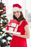Brunette in red dress holding pile of gift