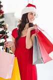 Brunette in red dress holding shopping bags