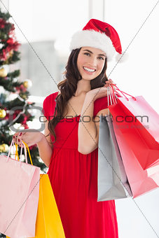 Smiling brunette in red dress holding shopping bags