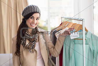 Smiling brunette holding price tag on shirt