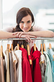 Pretty brunette smiling at camera by clothes rail