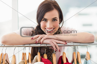 Smiling brunette smiling at camera by clothes rail