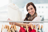 Smiling shopping brunette looking at dress