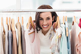 Beauty brunette smiling at camera by clothes rail