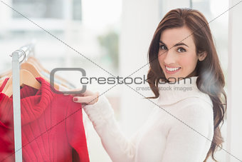 Smiling brunette looking at clothes on rail