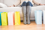 Woman sitting on couch with shopping bags