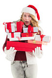 Blonde woman in trouble holding pile of gifts