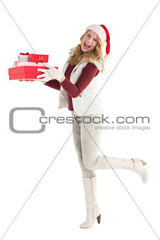 Smiling blonde in warm clothing holding pile of gifts