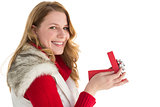 Surprised woman opening gift while looking at camera