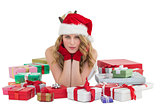 Woman in santa hat laying on the floor with gifts around her