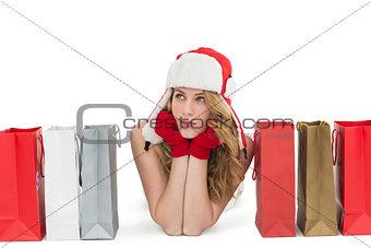 Thoughtful woman lying between shopping bags
