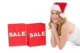Festive blonde lying with sale shopping bags