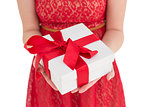 Pretty woman in red dress offering present