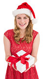 Smiling pretty woman in red dress offering present