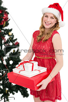 Blonde holding pile of gifts with christmas tree behind her