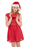 Blonde woman in santa hat standing with gift
