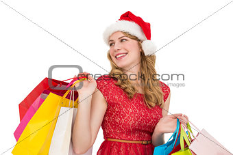 Smiling blonde in santa hat holding shopping bags