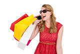 Pretty blonde talking on phone holding shopping bags