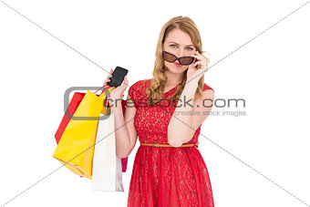 Cute woman holding shopping bags and her smartphone
