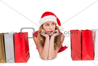 Thoughtful woman lying between shopping bags