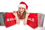 Smiling woman lying between sale shopping bags