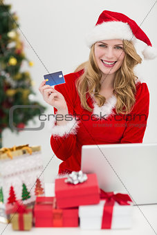 Blonde shopping online with laptop while smiling at camera