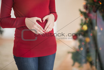 Close up of a pregnant woman making a heart on her belly