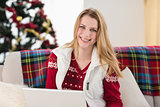 Smiling woman sitting on couch using her laptop