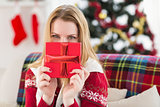 Young woman hiding behind a gift