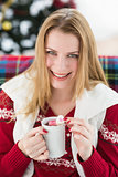 Smiling blonde in winter clothes holding mug