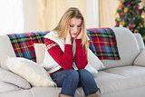 Woman with headache sitting on sofa