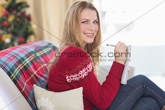 Smiling blonde writing while sitting on the sofa