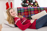 Smiling woman lying on couch while looking at camera