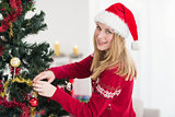 Woman decorating a Christmas tree while looking at camera