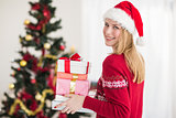 Blonde holding pile of gifts in front of the christmas tree