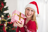 Smiling festive woman showing a pink gift