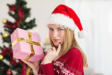 Festive woman standing holding a pink gift
