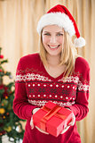 Festive pretty blonde woman offering gift