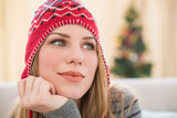 Woman in winter hat thinking with head on hand