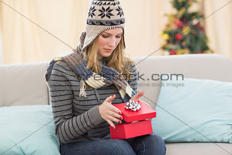 Blond woman opening a gift sitting on a sofa