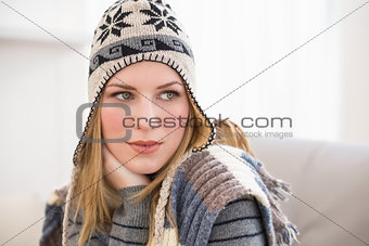 Beautiful blonde in winter hat thinking and looking away
